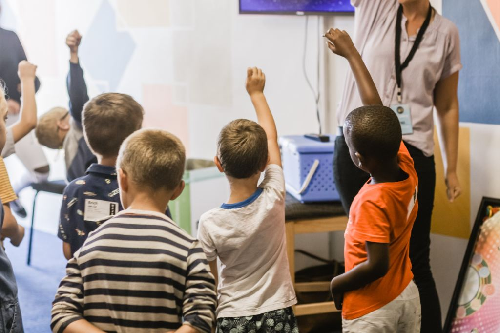Children raising their hands in a classroom Photo by Nicole Honeywill on Unsplash